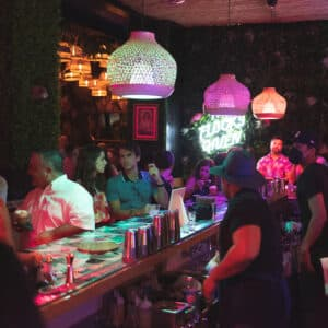 This is an image of Tipsy Flamingo in Downtown Miami. It shows a bartender behind the bar preparing a cocktail for a guest.