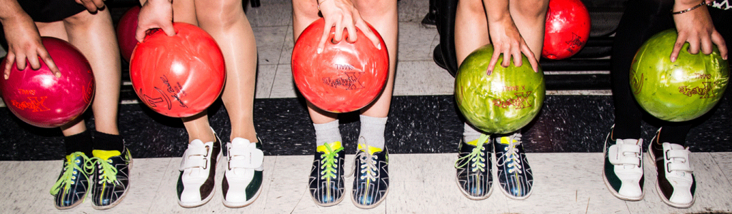 Line of people holding bowling balls