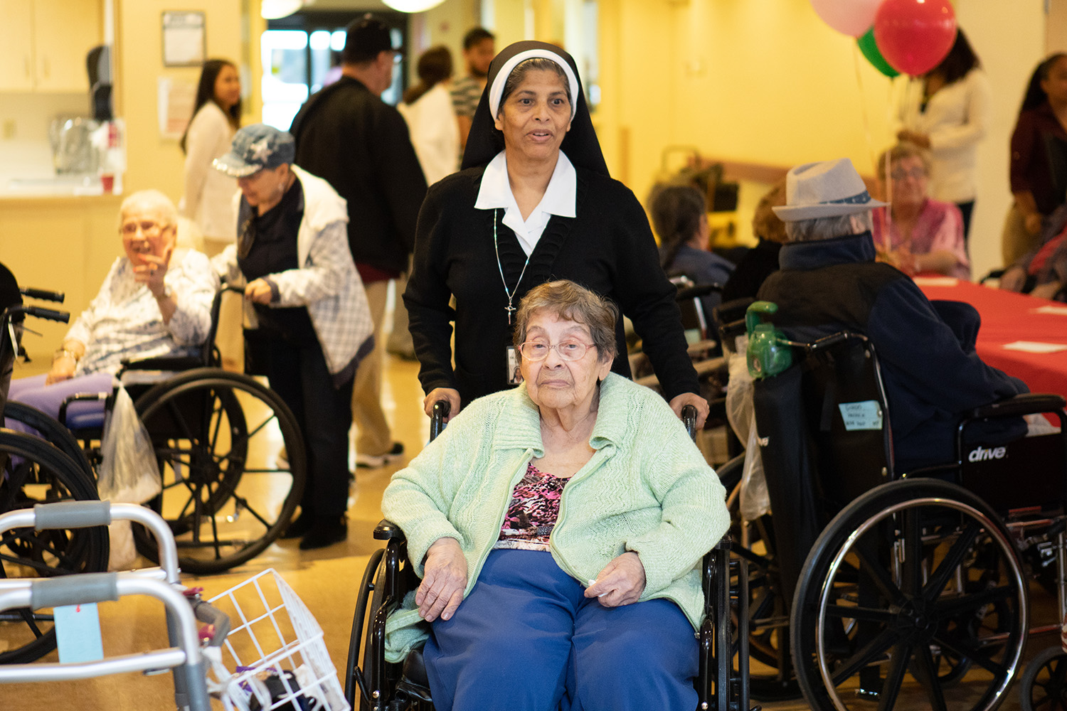 A nun escorting a female senior patient through a social gathering with other senior patients.