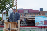 Doug Ruth stands and a podium wearing a white hard hat and a suit and tie. To his left, there is a rendering of the new Engineering Information and Technology Complex.