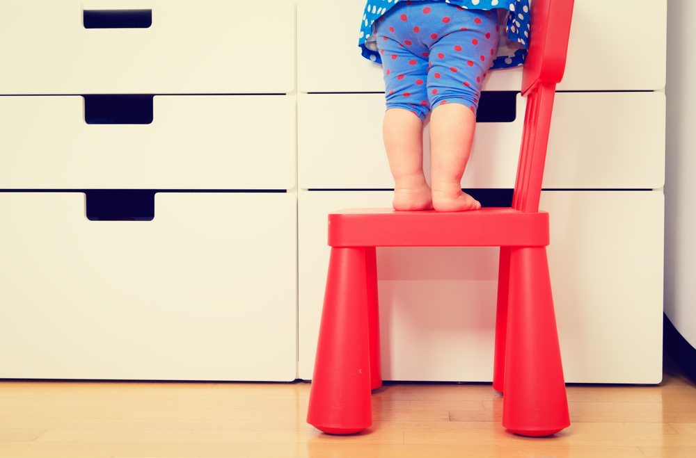 baby or toddler standing precariously on a chair