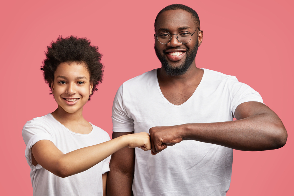 A father and son bump fists as a sign of mutual respect