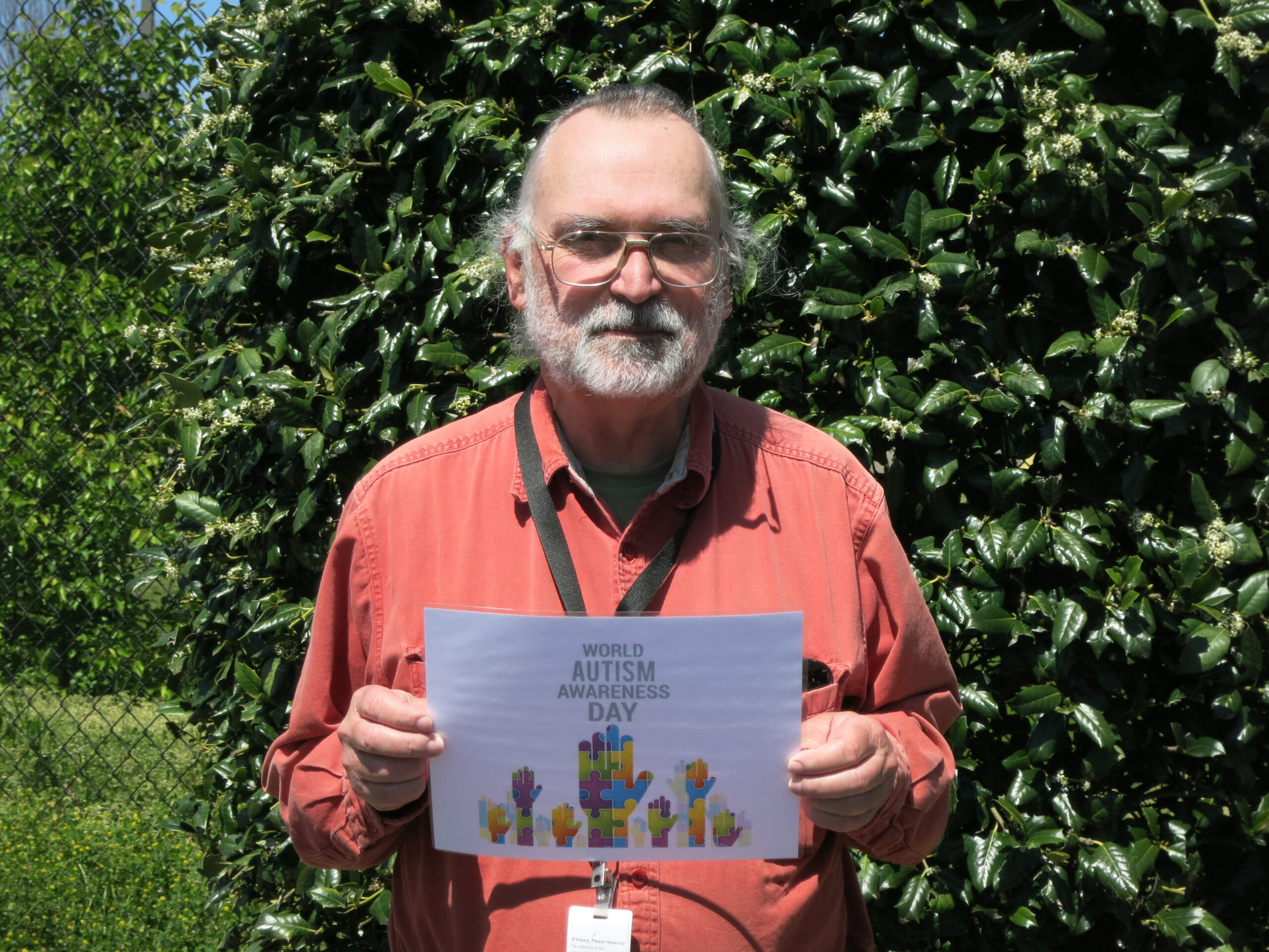 Tec-Masters' employee Dean Heston holding a sign of encouragement for our Autism walk.