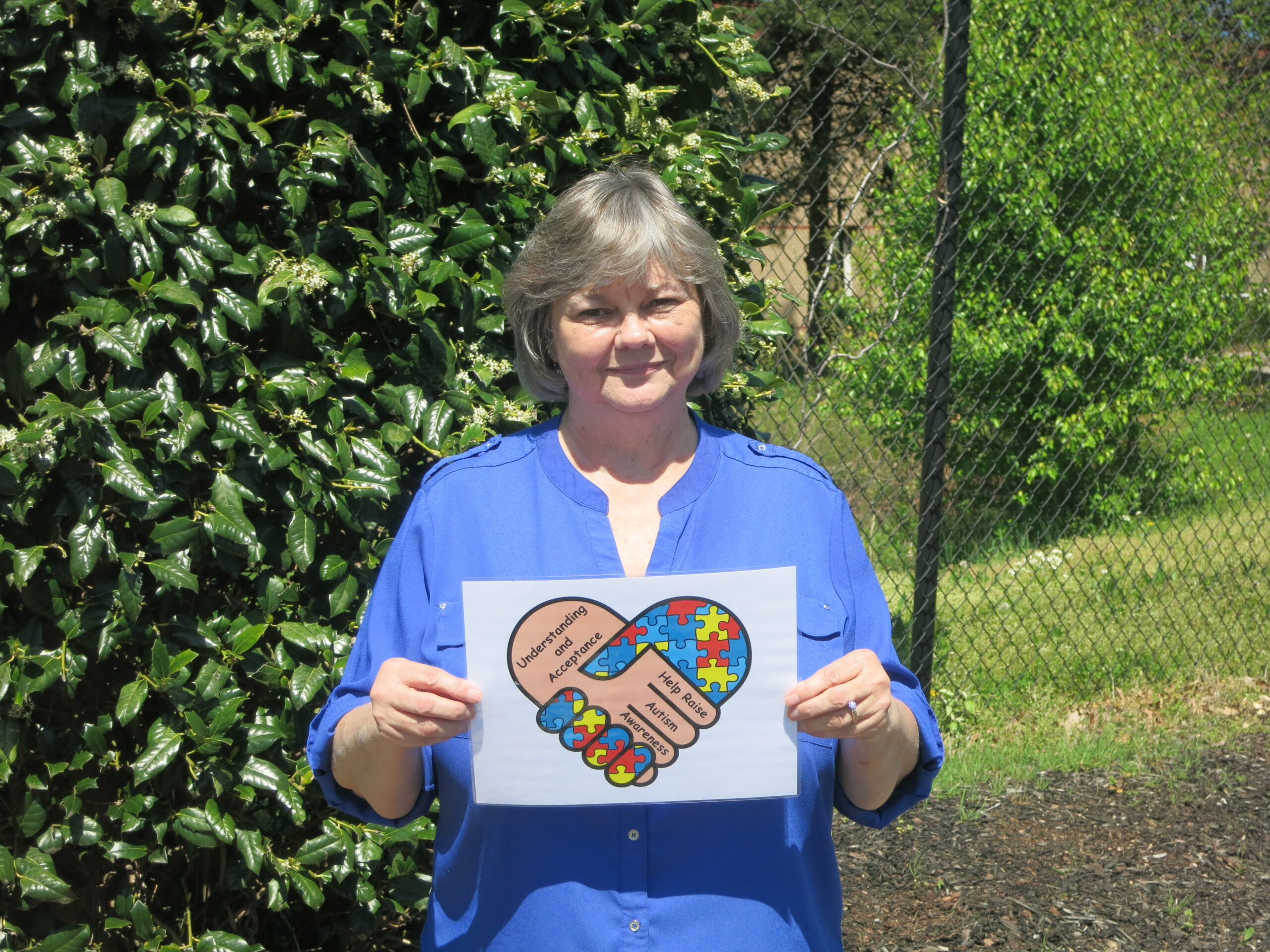 Tec-Masters' employee Mala Thompson holding a sign of encouragement for our Autism walk.