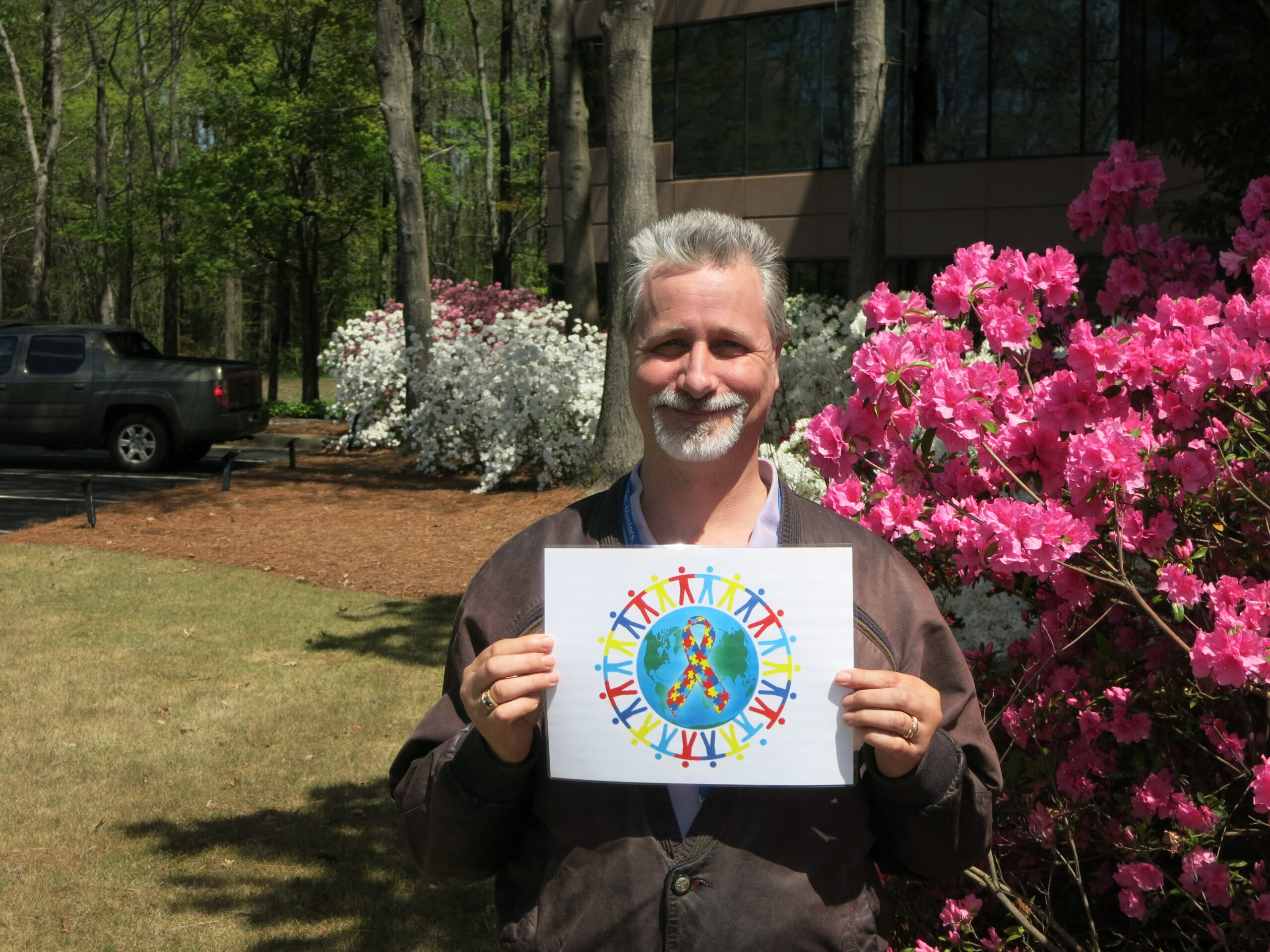 Tec-Masters' employee Martin Michel holding a sign of encouragement for our Autism walk.