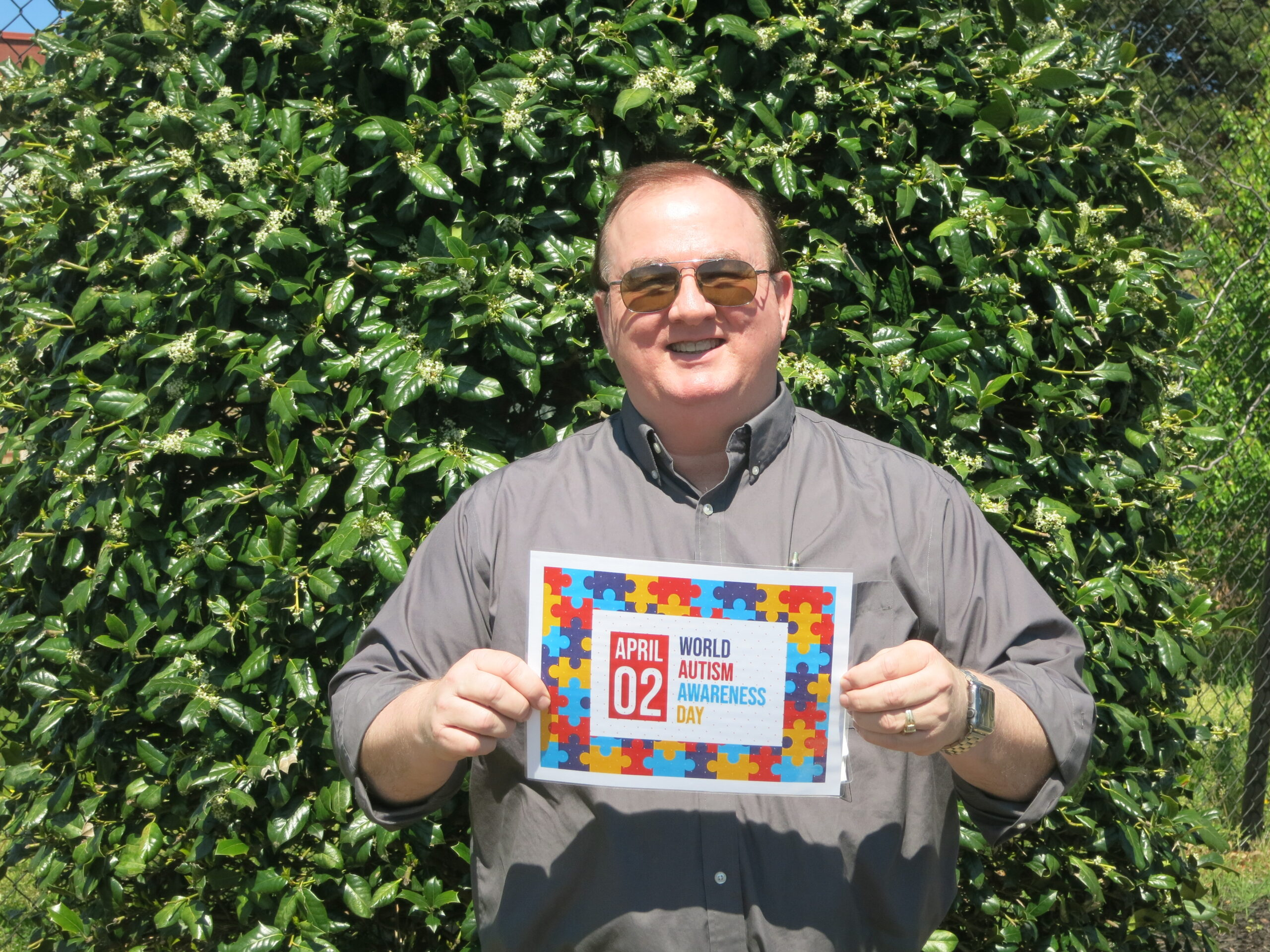 Tec-Masters' employee Scott Gilley holding a sign of encouragement for our Autism walk.