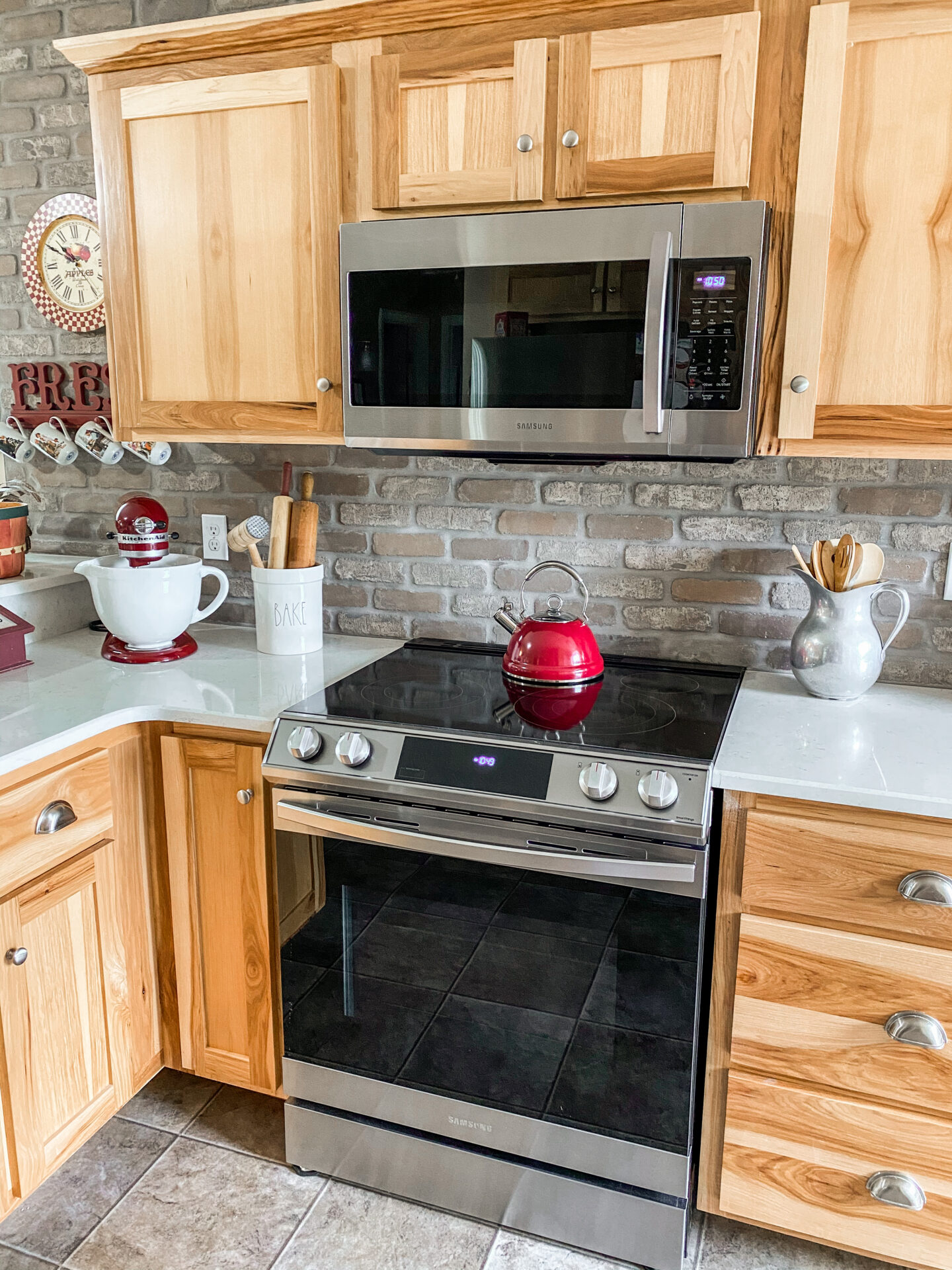 Country Kitchen with brick wall backsplash, kitchenaid stand mixer and antiques.