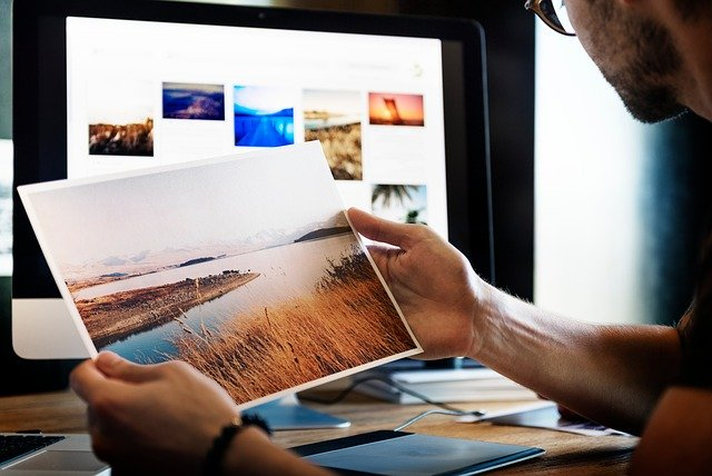 Person at a computer looking at images and holding a photograph.