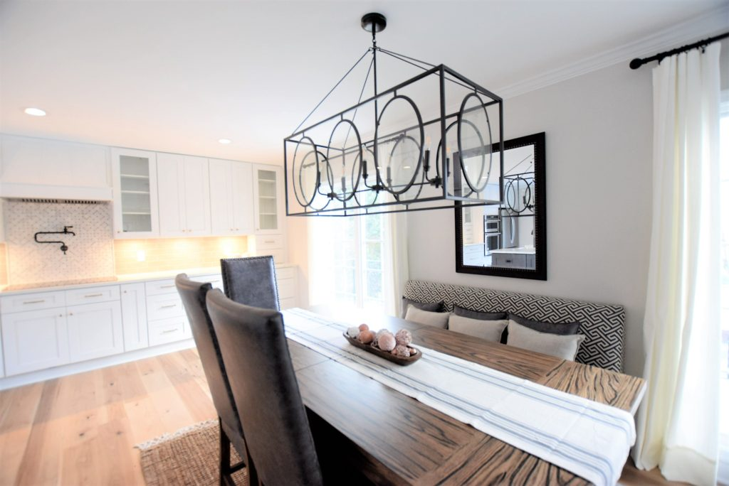 Ballard designs chandelier Calcatta laza Quartz by MSI,  ice white shaker cabinets, engineered wide plank flooring, Kitchen Aid Appliances, induction cooktop, large farmhouse table, kitchen banquette seating