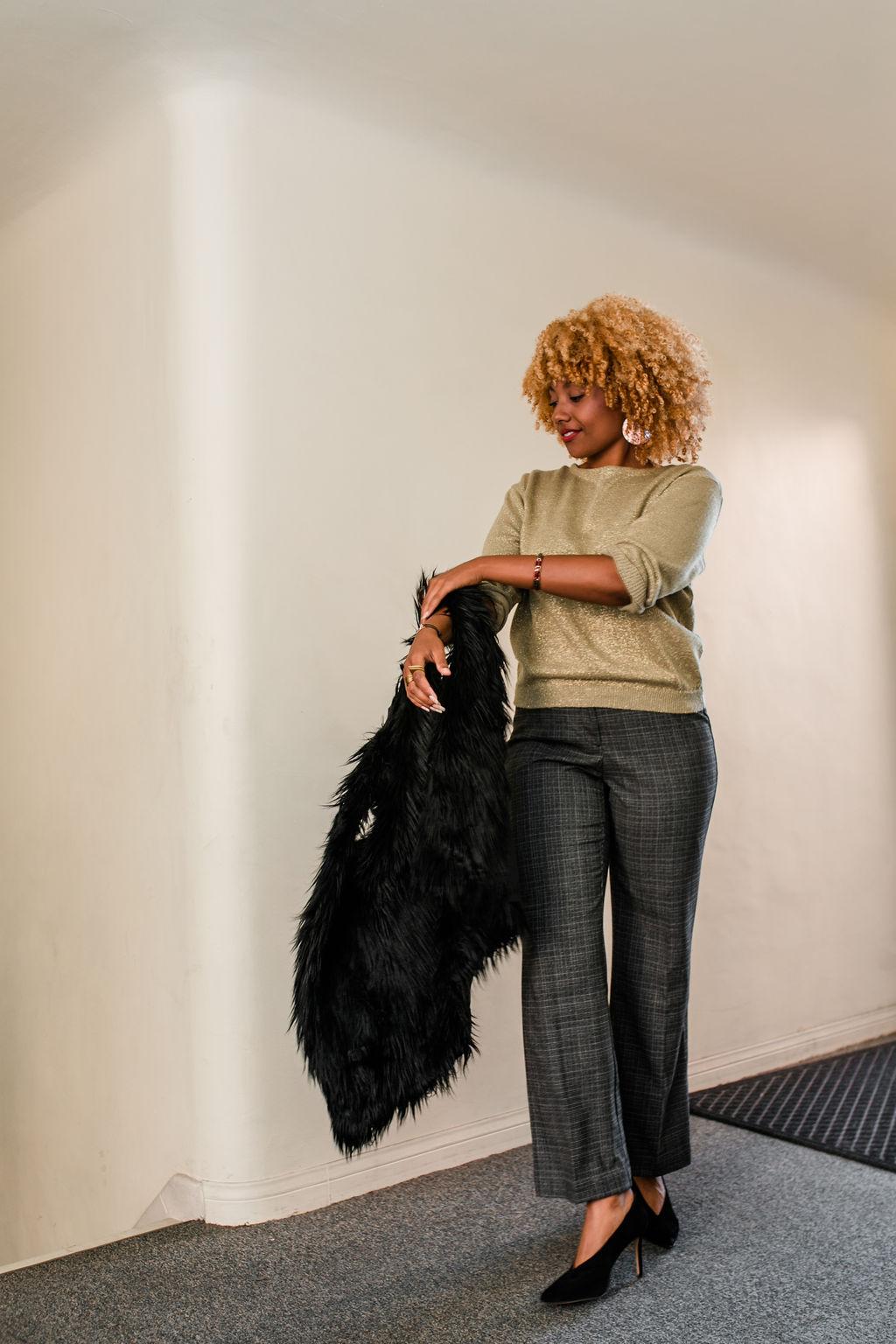 black women taking off fur vest wearing slacks and black high heels - reflect