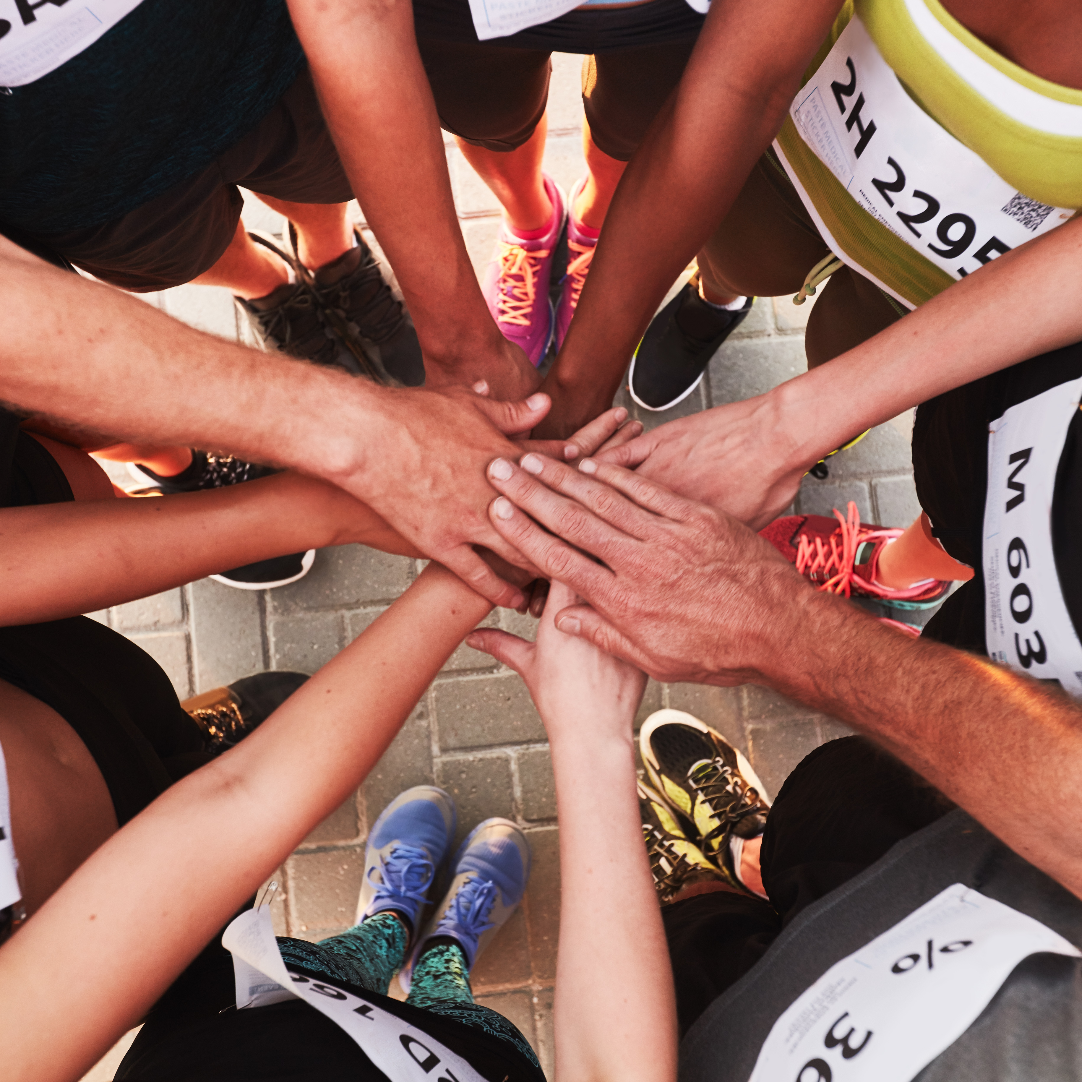 Hands of running team stacked on top of each other