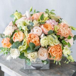 Bouquet of fresh spring flowers on gray wall background. Floral arrangement in vintage metal vase. flower shop, florist work.