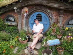 Guy sitting in front of a Hobbit's door