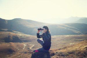 a woman crouching on a mountain looking into binoculars
