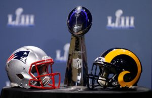 Patriots helmet and rams helmet sit on a table facing each other in front of superbowl trophy.