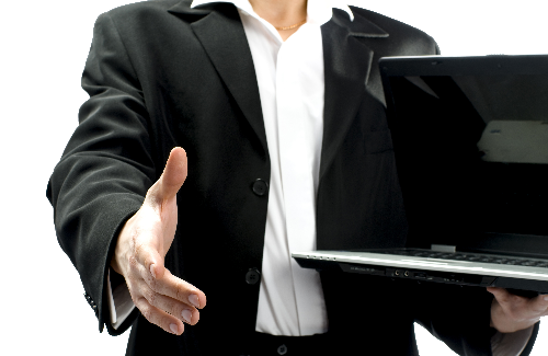 IT professional reaching out to shake hands while holding a laptop computer