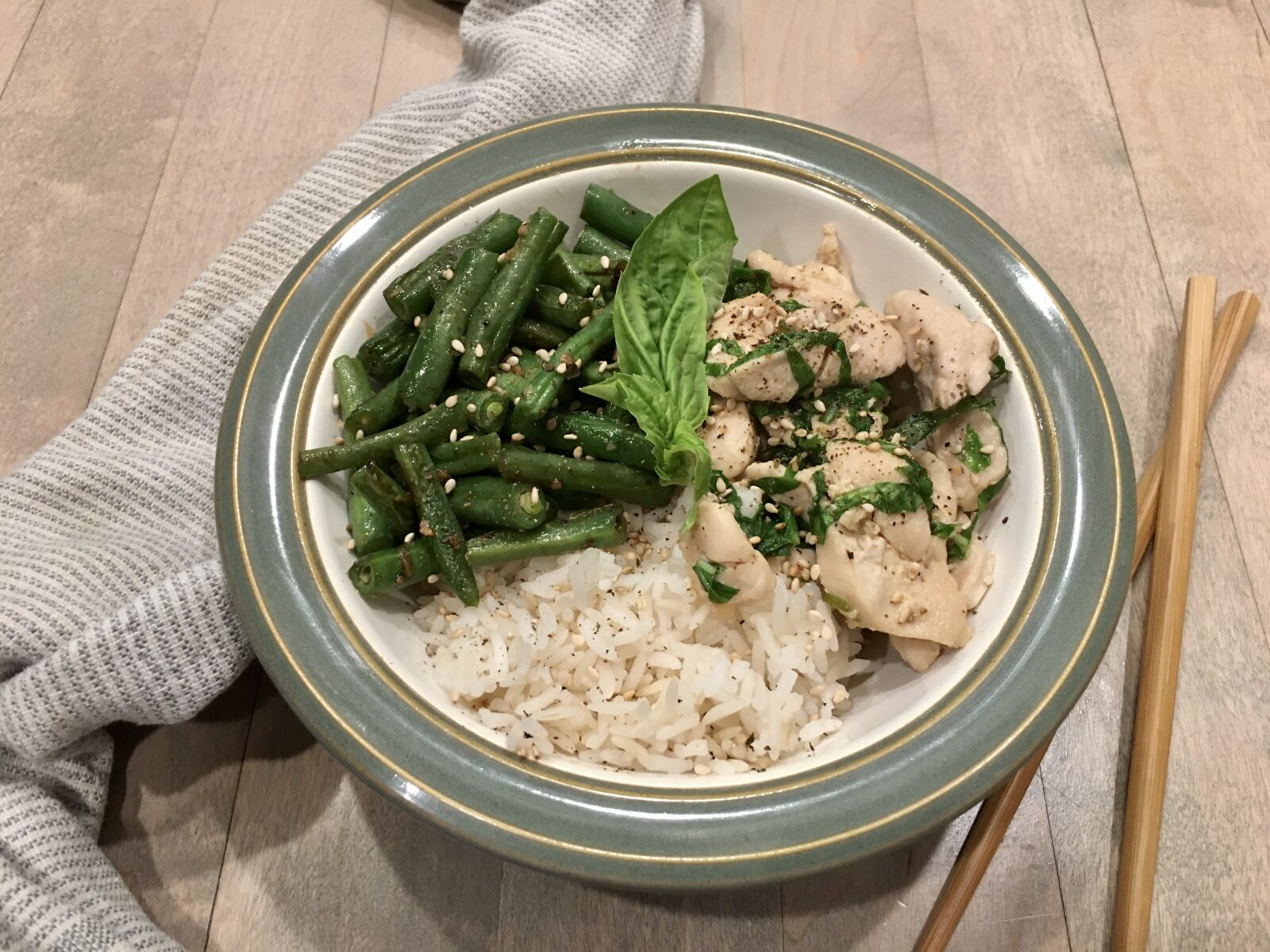 Chile, Basil & Chicken Stir-fry served in a bowl with a towel and chop sticks