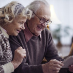 Elderly husband and wife networking at home