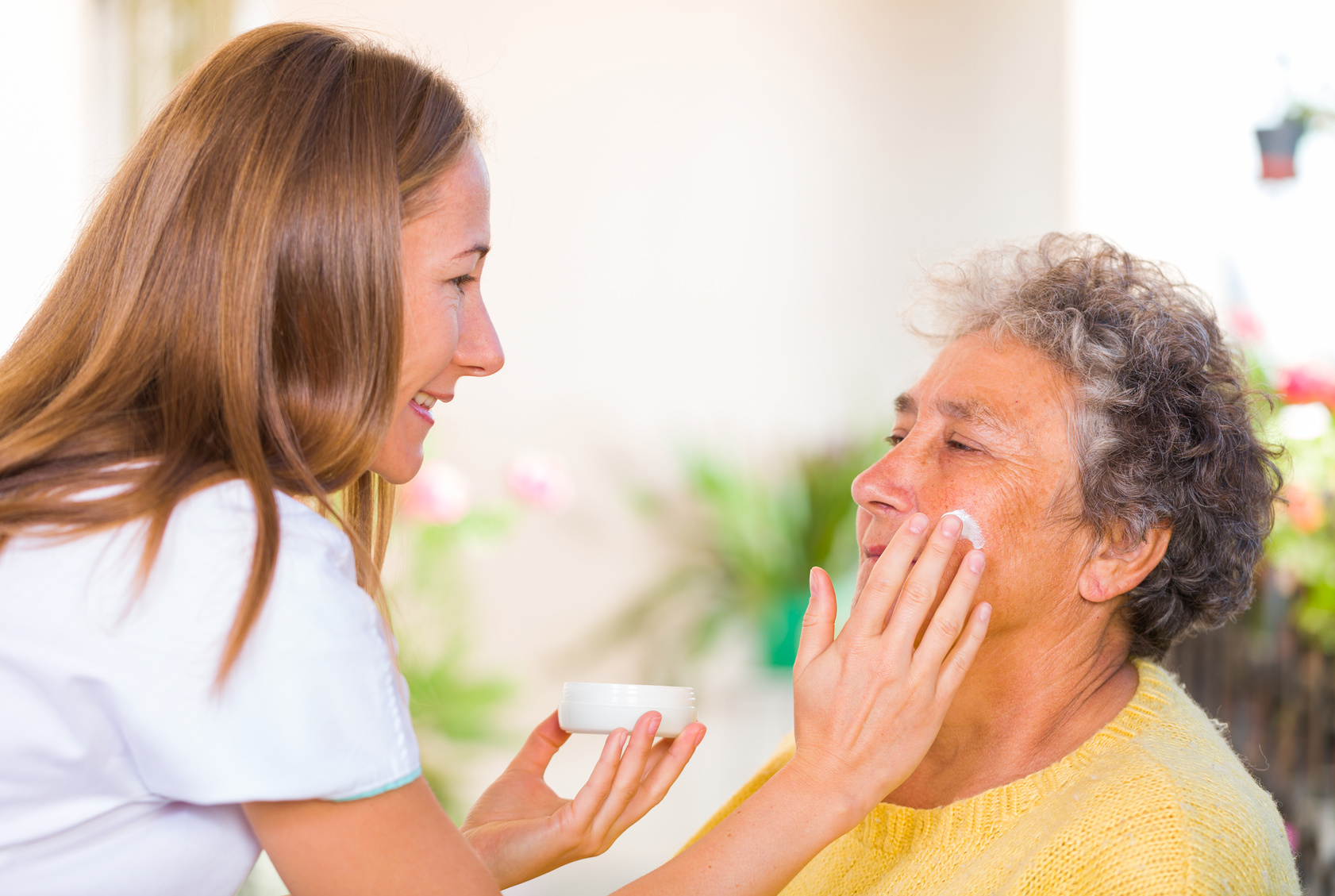Caregiver rubs the face cream on the elderly womans face