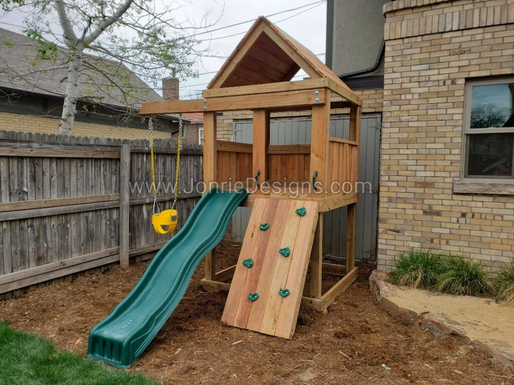 5'x5' Clubhouse with wooden roof, 4' Deck height, Standard slide, Rock wall entry, 3' Cantilever with yellow bucket swing