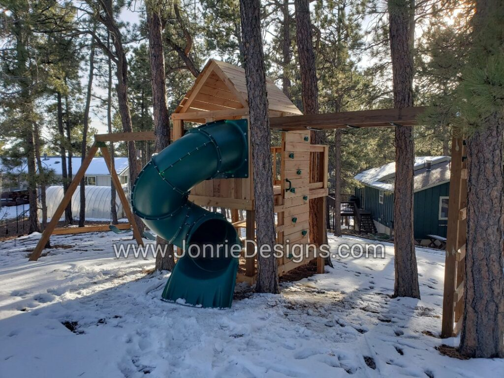 5'x5' Clubhouse with wooden roof with 3'x5' Uncovered porch with baluster rails (5'x8' Footprint), 4' Deck height, 5' Enclosed spiral slide, 8' Climbing wall, 8' Swing beam with 2 Standard swings