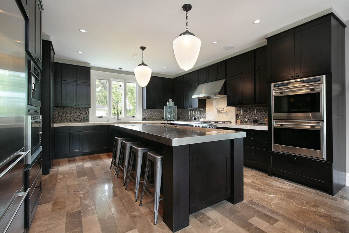 Kitchen in luxury home with dark wood cabinetry