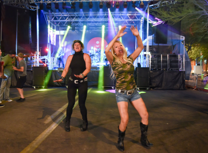 Two girls dancing at a concert.