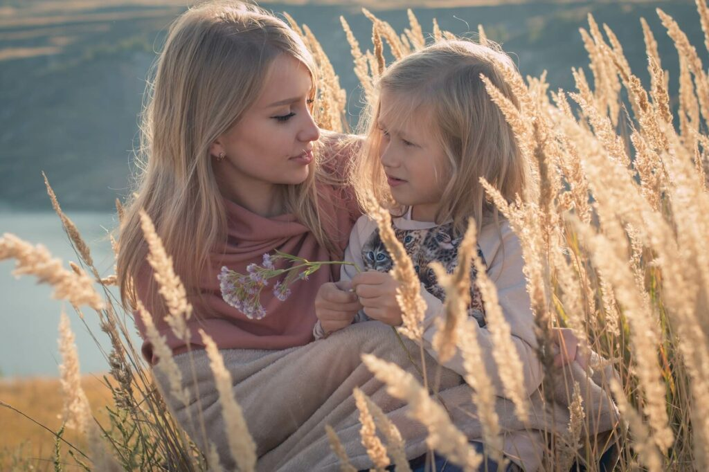 Mom Holds Young Daughter in Field