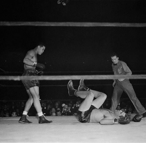 Original caption: New York, New York: Louis Wins In First Over Baer. Joe Louis battered Buddy Baer to the canvas only 2 minutes and 56 seconds after the fight, for Navy relief in the Madison Square garden, Jan. 9, began. Photo shows Baer as he landed on his back on the canvas after a flock of right uppercuts by Louis (Left) had landed him there in final knockout. Referee Frankie Fullam is at right. January 9, 1942 Manhattan, New York, New York, USA