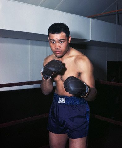 """USA --- Boxing great Joe Louis, the """"Brown Bomber"""", stands in a gymnasium boxing ring as if ready for a match. --- Image by © Bettmann/CORBIS"""