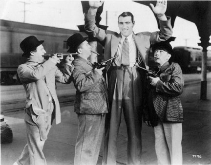 Heavyweight Champion Primo Carnera being held up by none other than the Three Stooges