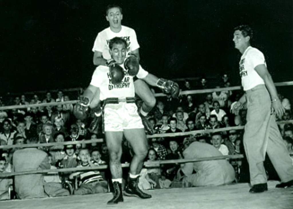 Jerry Lewis rides on back of Rocky Marciano as Dean Martin looks on