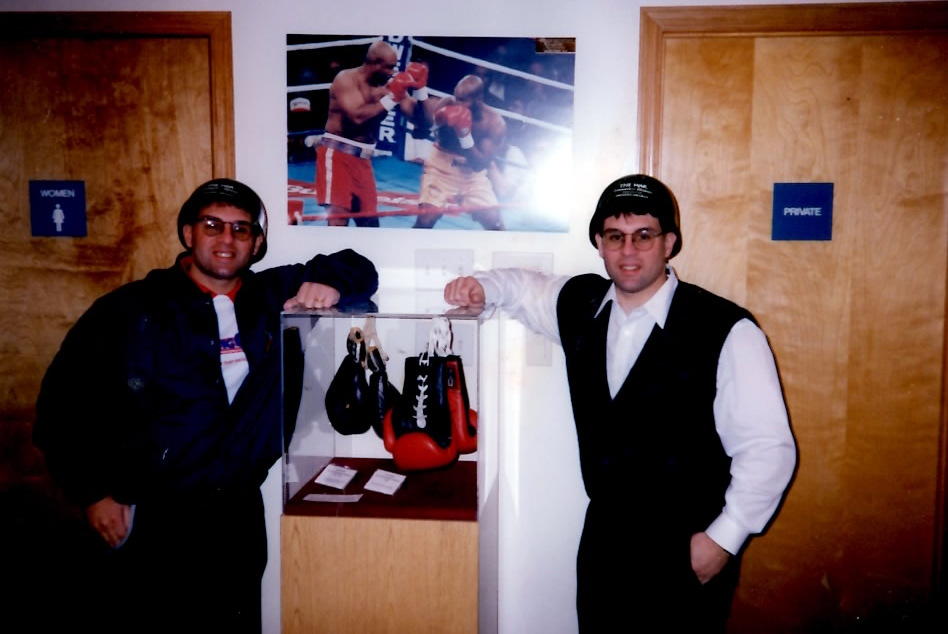 """The Boxing Twins wearing Leonard-Hearns II promotional """"WAR"""" army helmits standing next to Alex's photo of the Foreman-Moorer bout displayed in the Boxing Hall of Fame"""