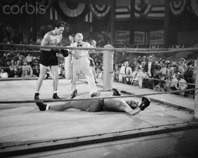 17 Jul 1942, Hollywood, Los Angeles, California, USA --- Original caption: Errol Flynn Collapses on Set. Hollywood, California: A moment after this fight scene was taken, actor Errol Flynn (left) collapsed on the set at Hollywood Studio, and was rushed to the hospital suffering from nervous exhaustion. Flynn is pictured portraying the character of famed old-time fighter, James J. Corbett. --- Image by © Bettmann/CORBIS