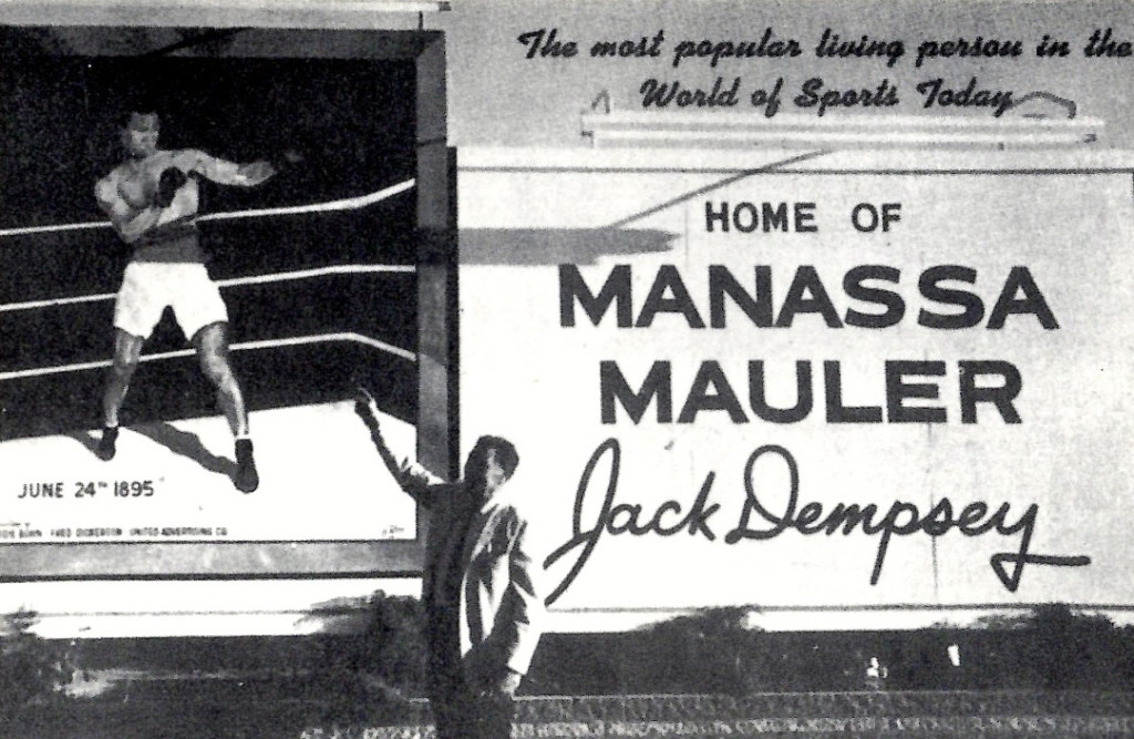 Jack Dempsey standing by sign in his hometown of Massassa, Colorado