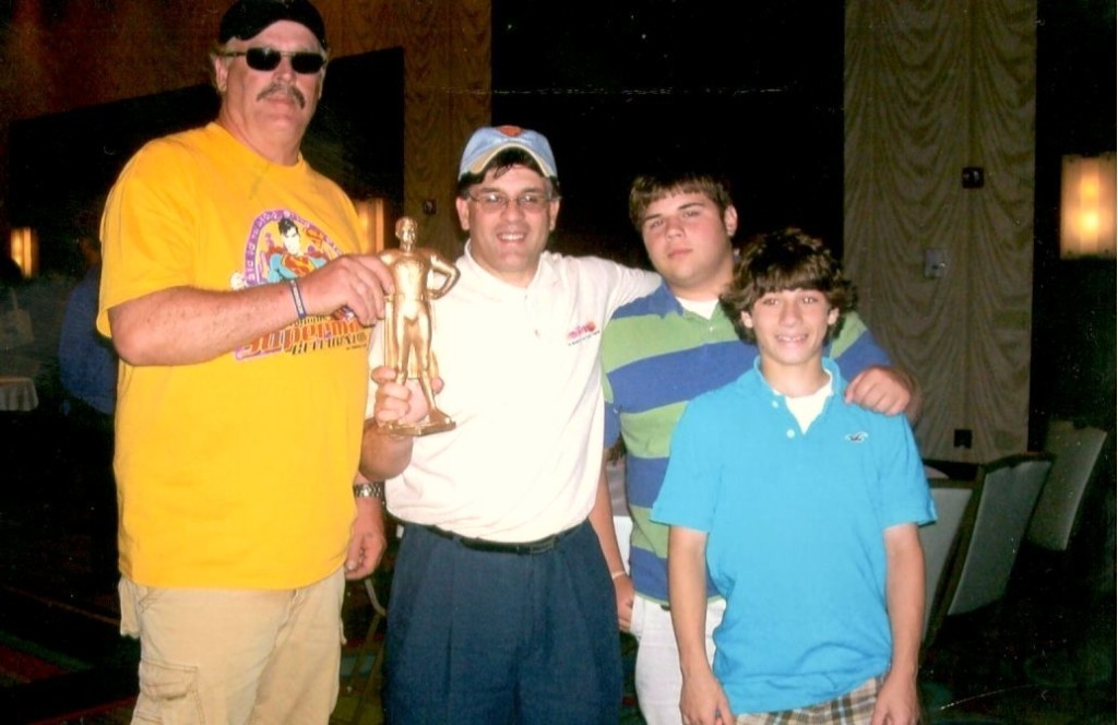 """Jim Hambrick presents the prestigious George """"Superman"""" reeves Award known as the """"George"""" Award to Alex Rinaldi who is flanked by his sons Ron John and Alexander."""