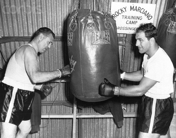 02 Sep 1954, Grossinger, New York State, USA --- Original caption: 9/2/1954-Grossinger, NY- Former heavyweight champion Jack Dempsey gets in a few licks for old times sake, as champ Rocky Marciano steadies the heavy bag for him at Rocky's training camp. Dempsey visited Marciano to watch him train for his forthcoming return bout with Ezzard Charles at Yankee Stadium September 15th. --- Image by © Bettmann/CORBIS