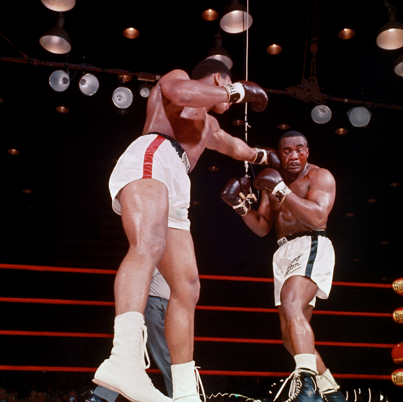 Boxer Muhammad Ali, aka Cassius Clay (R), punching Sonny Liston during heavyweight championship bout.