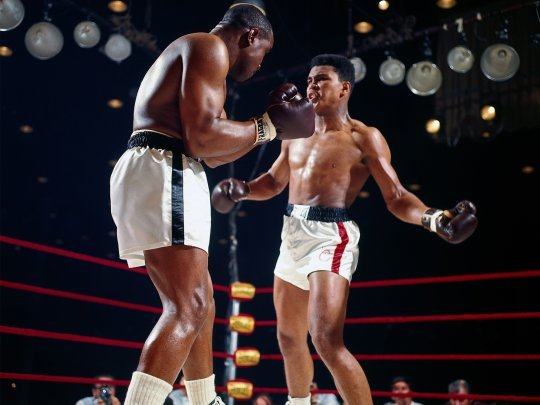 Muhammad Ali (Casius clay) (R) loads up with a left hook at Sonny Liston (L)