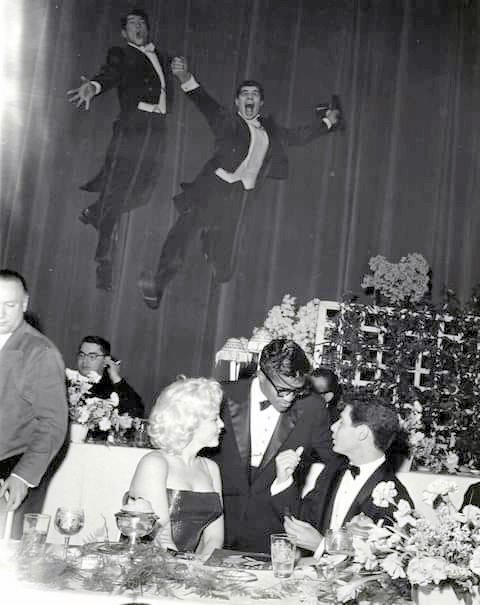 Dean Martin and jerry Lewis are flying in the air while Marilyn Monroe chats with Sammy Davis Jr and Eddie Fisher at the Friars Club – 1955