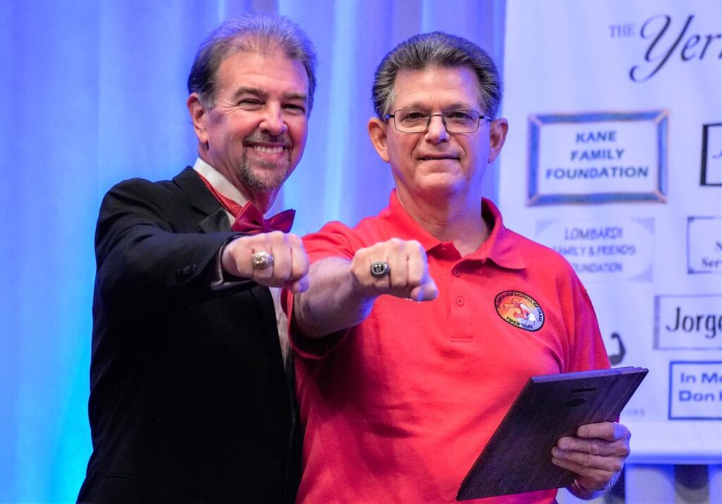 L-R FLBHOF Announcer Bob Alexander with 2020 Inductee referee Emil Lombardi, Jr. showing off their FLBHOF Championship Rings.