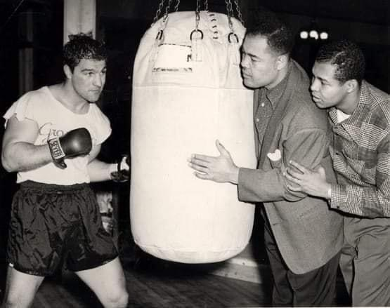 Heavyweight Champion Rocky Marciano in training with former Heavyweight Champion Joe Louis holding the bag.