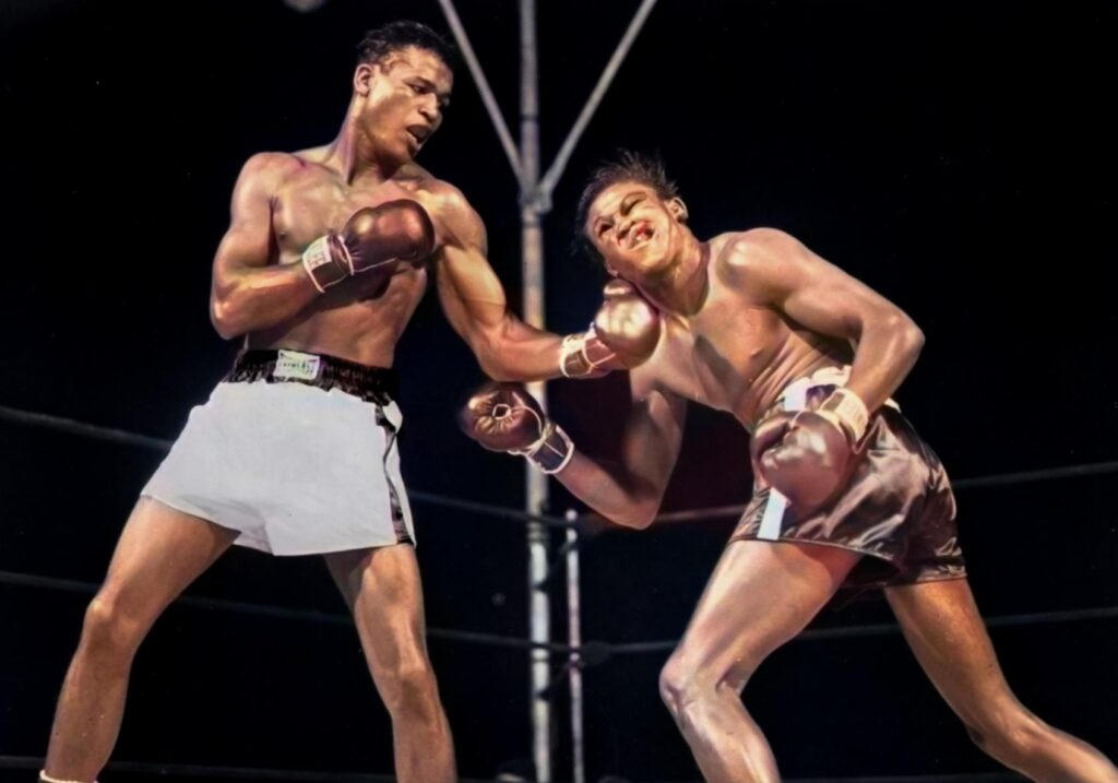 Sugar Ray Robinson (L) connecting with a hard left hook to the jaw in their July 11, 1949 Welterweight Championship at Philadelphia Municipal Stadium where Robison retained his title via a 15th round decision.