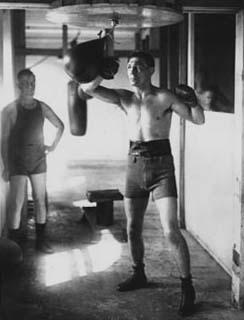 Middleweight Champion Harry Greb working out with the speed bag.