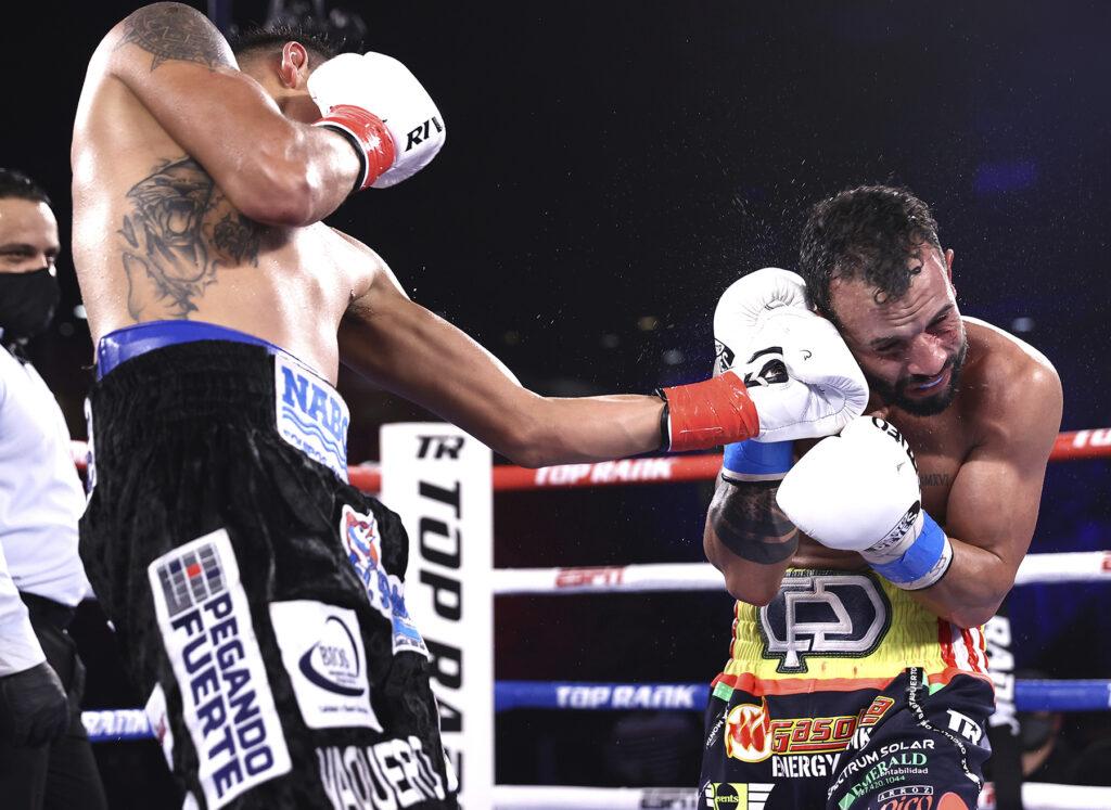 Emanuel Navarrete (L) landing a left uppercut to the chin of Christopher Diaz (R) .