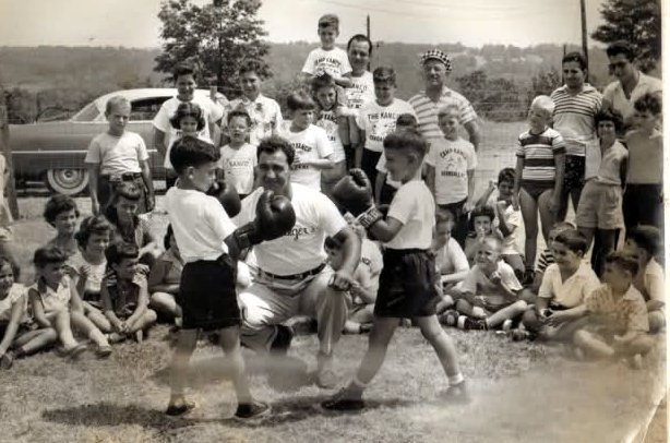 Heavyweight Champion Rocky Marciano teaching some youngsters how to box.