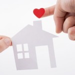 Paper house and  heart shape in hand on a white background