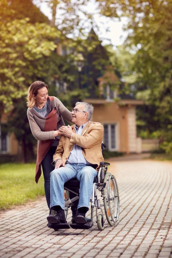 an elderly man in a wheelchair and a woman