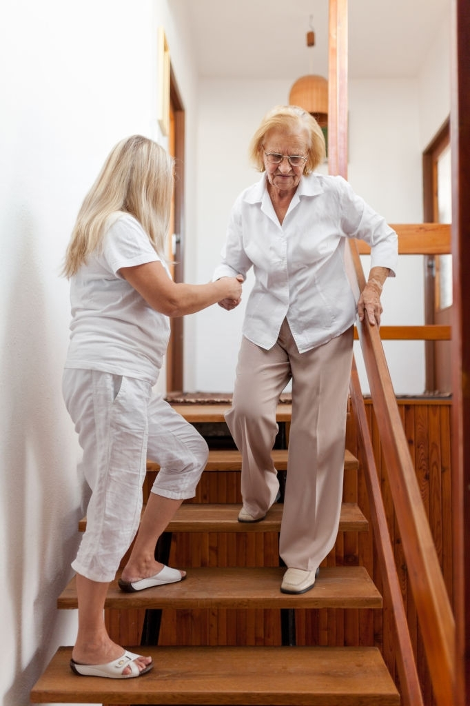 a younger woman helping an elderly woman in going down the stairs