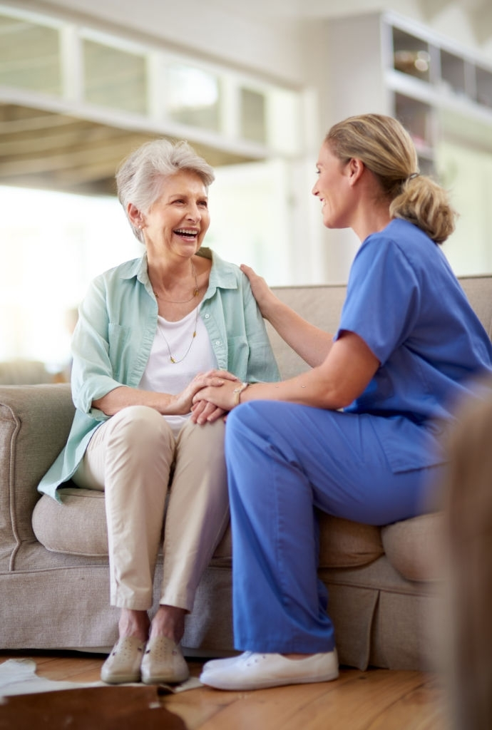 an elderly woman talking to a female medical professional in blue scrubs